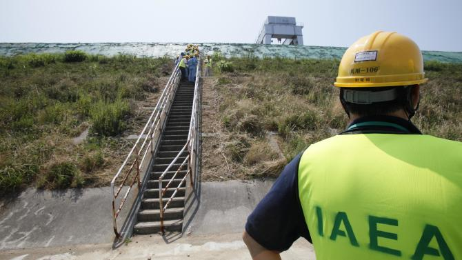 Experts from the International Atomic Energy Agency inspect the anti-tsumani wall at the Onagawa nuclear power plant in Onagawa, Miyagi prefecture, northeastern Japan, Tuesday, July 31, 2012. The 20-member IAEA mission, first at the Onagawa nuclear power plant, about 120 kilometers (74 miles) north of Fukushima Dai-ichi nuclear plant, since the crisis, aims to find out the extent of damage at the plant from the magnitude 9.0 quake. (AP Photo/Koji Sasahara)