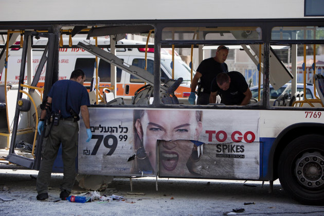 Israeli police officers examine a blown up bus at the site of a bombing in Tel Aviv, Israel, Wednesday, Nov. 21, 2012. A bomb ripped through an Israeli bus near the nation's military headquarters in T