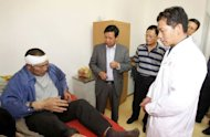 Chinese Ambassador to Zambia Zhou Yuxiao (C) visits a victim of the Collum Coal mine wages riot at Levy Mwanawasa Hospital on August 6, 2012 in Lusaka. The killing of a Chinese mine boss last weekend has left Zambian President Michael Sata&#39;s government rushing to reassure foreign investors on their safety