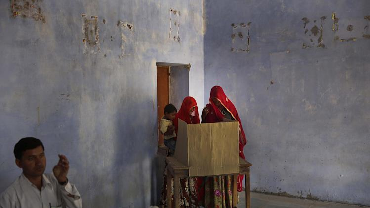 Indian women cast their vote during the sixth phase of polling of the Indian parliamentary elections at a village near Sawai Madhopur, Rajasthan state, India, Thursday, April 24, 2014. With 814 million eligible voters, India is voting in phases over six weeks. Results are expected May 16. (AP Photo /Manish Swarup)