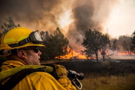 A firefighter watches for spot fires at the Rocky Fire in Lake County, California