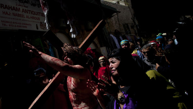 A Christian pilgrim dressed as Jesus Christ carries a cross during a reenactment of the crucifixion during a Good Friday procession in Jerusalem's Old City, Friday, March 29, 2013.  Less than 2 percent of the population of Israel and the Palestinian territories is Christian, mostly split between Catholicism and Orthodox streams of Christianity. Christians in the West Bank wanting to attend services in Jerusalem must obtain permission from Israeli authorities. Israel's Tourism Ministry said it expects some 150,000 visitors in Israel during Easter week and the Jewish festival of Passover, which coincide this year. (AP Photo/Sebastian Scheiner)