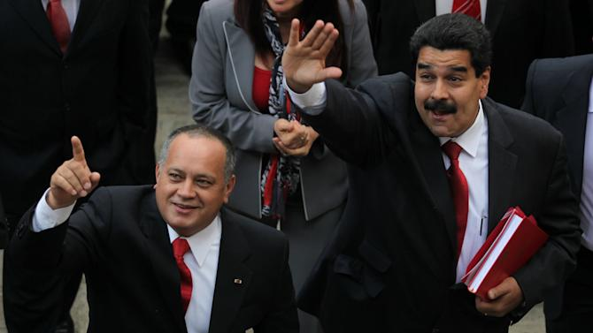 Venezuela's Vice President Nicolas Maduro, right, and Diosdado Cabello, President of Venezuela's National Assembly, gesture to supporters upon their arrival to attend the state-of-the-nation address  in Caracas, Venezuela, Tuesday, Jan. 15, 2013. Maduro submitted the report in writing from ailing President Hugo Chavez, who is receiving treatment in Cuba after undergoing his fourth cancer surgery. Opposition politicians had argued that lawmakers should have postponed the annual speech because Chavez was supposed to deliver it. (AP Photo/Fernando Llano)