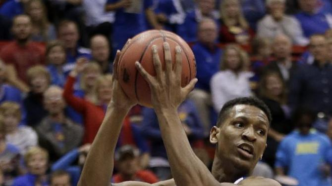 Kansas' Andrew White III grabs a rebound during the first half of an NCAA college basketball game against Towson Friday, Nov. 22, 2013 in Lawrence, Kan. Kansas won the game 88-58