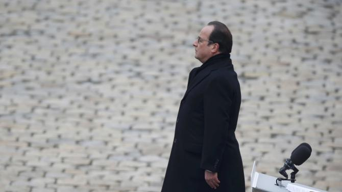 French President Francois Hollande stands at attention during a ceremony to pay a national homage to the victims of the Paris attacks at Les Invalides monument in Paris