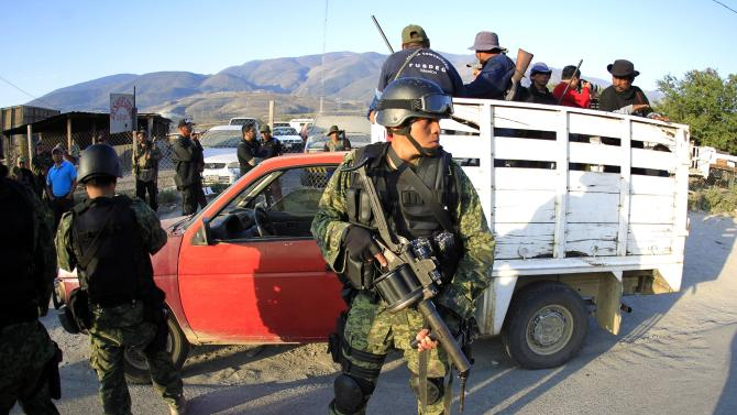 Members of the Community Police from the FUSDEG are seen in a truck behind soldiers of the Mexican Army, in the early morning at an entry to Petaquillas
