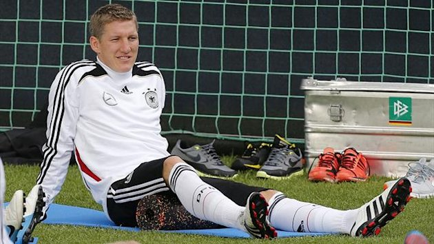 Bastian Schweinsteiger relaxes during training (Reuters)