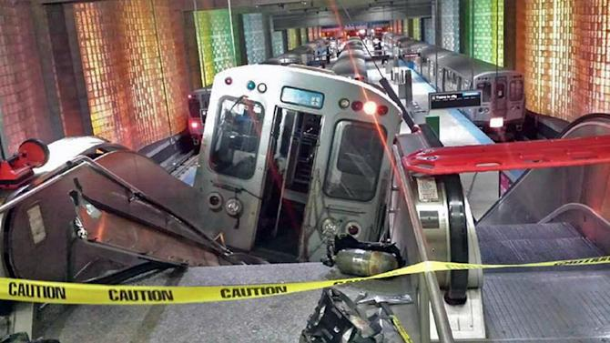 """A Chicago Transit Authority train car rests on an escalator at the O'Hare Airport station after it derailed early Monday, March 24, 2014, in Chicago. More than 30 people were injured after the train """"climbed over the last stop, jumped up on the sidewalk and then went up the stairs and escalator,"""" according to Chicago Fire Commissioner Jose Santiago. (AP Photo/NBC Chicago, Kenneth Webster) MANDATORY CREDIT"""
