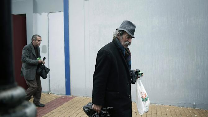 A man carry bags of donated food as he leaves with a meal for the homeless organized by the municipality of Athens on Wednesday Jan. 1, 2014. Homelessness has increased dramatically during the financial crisis in Greece, which has depended on international rescue loans for more than three years. (AP Photo/Petros Giannakouris)
