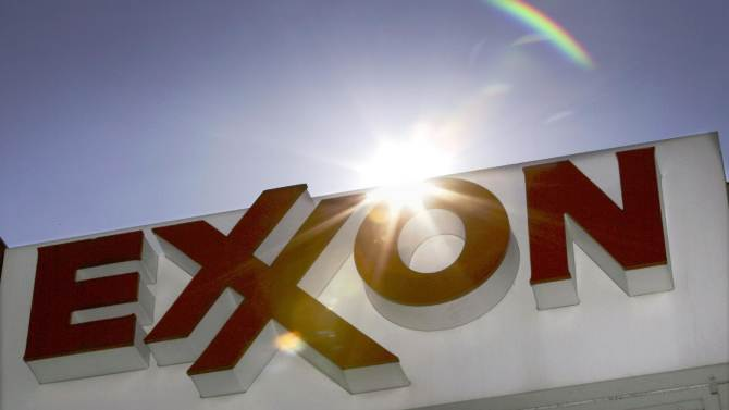 FILE - This file photo taken, Oct. 26, 2006, shows an Exxon logo seen at a Dallas gas station. Exxon expects to see more and more hybrids on the world's roads, with gas-sipping models like the Toyota Prius making up half of all vehicles by 2040. The largest publicly traded oil and gas company says in its annual energy outlook that the use of hybrids _ vehicles that rely on both gas and electricity for power _ and other efficiency gains will keep energy demand in check for the U.S. and other major industrialized countries for years. (AP Photo/LM Otero, File)