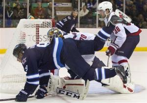 Winnipeg Jets Evander Kane is tripped up by Washington Capitals goalie Branden Holtby in Belleville.