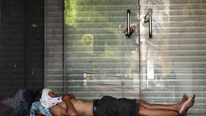 A man sleeps in a doorway at a temple on Chap Goh Meh, in Kuala Lumpur