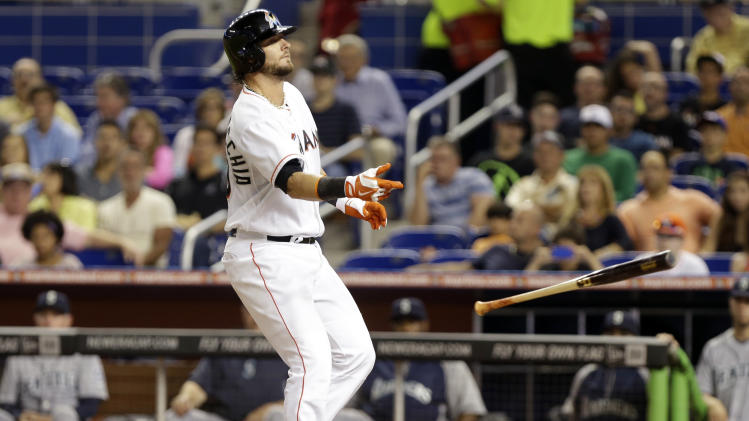 Miami Marlins' Jarrod Saltalamacchia tosses his bat after drawing a walk during the first inning of an interleague baseball game against the Seattle Mariners, Friday, April 18, 2014, in Miami. (AP Photo/Lynne Sladky)