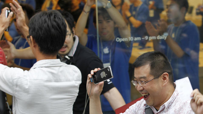 Customers celebrate as Apple Inc. started selling iPhone 5 at a store in Tokyo Friday morning, Sept. 21, 2012. Apple's Asian fans jammed the tech juggernaut's shops in Australia, Hong Kong, Japan and Singapore to pick up the latest version of its iPhone. (AP Photo/Koji Sasahara)
