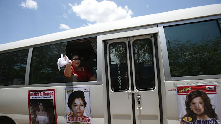 In this May 5, 2013 photo, former Philippine First Lady Imelda Marcos waves from her van with posters of her and daughter Imee during an electoral campaign in Ilocos Norte province, northern Philippines. Twenty-seven years after her dictator husband was ousted by a public revolt, Imelda Marcos has emerged as the Philippines' ultimate political survivor: She was back on the campaign trail this week, dazzling voters with her bouffant hairstyle, oversized jewelry and big talk in a bid to keep her seat in Congress. (AP Photo/Aaron Favila)