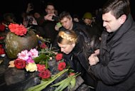 Newly freed Ukrainian opposition icon Yulia Tymoshenko kisses a flower as she visits the site where an opposition protester on Grushevsky street in Kiev on February 22, 2014