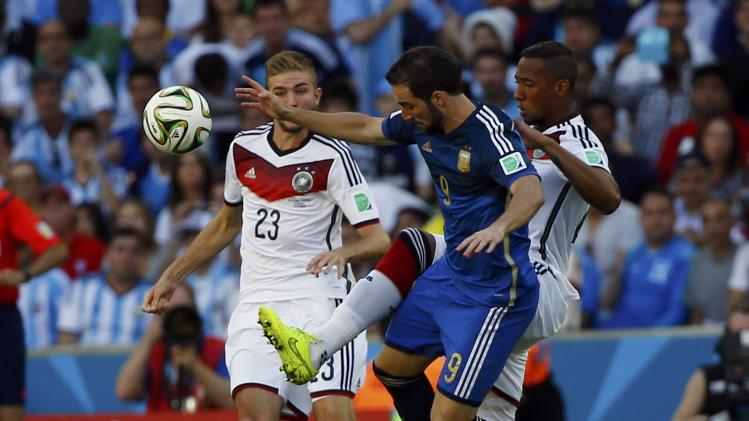 Argentina's Higuain fights for the ball with Germany's Kramer and Boateng during their 2014 World Cup final at the Maracana stadium in Rio de Janeiro