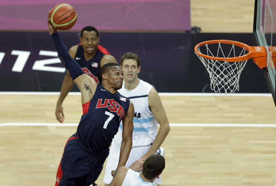 United States' Russell Westbrook (7) slams a dunk as Argentina's Hernan Jasen, top right, looks on during a preliminary basketball match at the 2012 Summer Olympics, Tuesday, Aug. 7, 2012, in London. (AP Photo/Victor R. Caivano)
