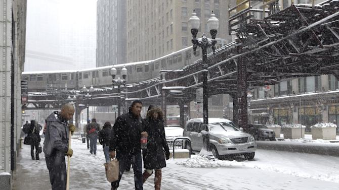 An El train runs through Chicago's downtown loop as a snow storm passes through the region Tuesday, March 5, 2013. Chicago was hit Tuesday by a storm expected to dump as much as 10 inches of snow in the area before the end of the day — the most since the 2011 blizzard and its more than 20 inches of snow. (AP Photo/Kiichiro Sato)