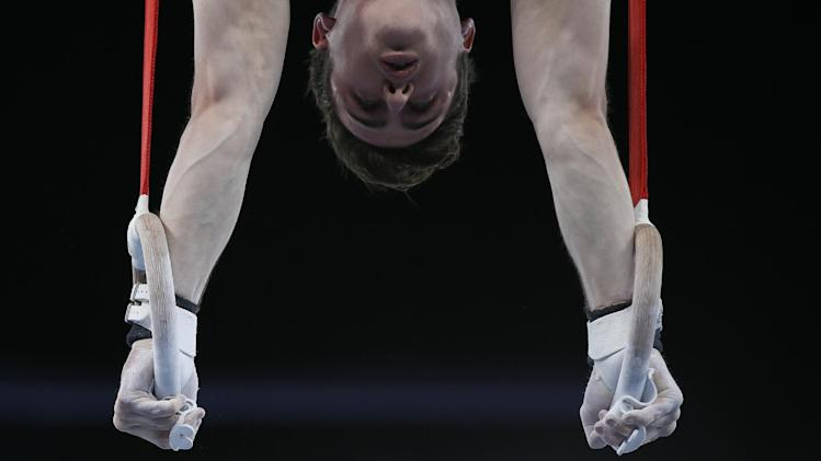 Jack Richards of Australia holds a position on the rings as he tales past in the me's team and individual qualification gymnastics competition at the Commonwealth Games Glasgow 2014, in Glasgow, Scotland, Monday, July, 28, 2014. (AP Photo/Alastair Grant)