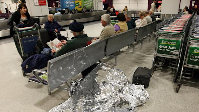 Passengers rest  as their flights have been canceled at Edinburgh Airport in Edinburgh, Scotland Tuesday, May 24, 2011. A dense ash cloud from an Icelandic volcano blew toward Scotland, causing airlines to cancel Tuesday flights and raising fears of a repeat of last year's huge travel disruptions in Europe that stranded millions of passengers. (AP Photo/Scott Heppell)