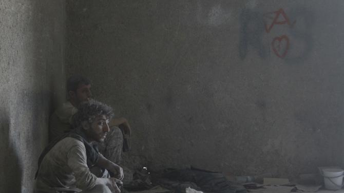 Free Syrian Army fighters rest inside a damaged room, during what activists said were clashes with forces loyal to Syria's President Bashar al-Assad in Al-Amiriya near the Artillery School in Aleppo
