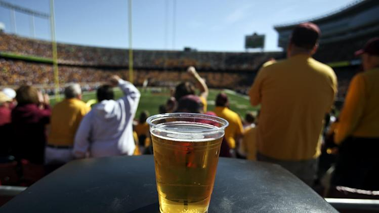 In this Sept. 8, 2012, photo, a beer sits atop a garbage can as Minnesota college football fans fans cheer a first quarter play against New Hampshire at TCF Bank Stadium in Minneapolis, Minn. A growing number of schools are capitalizing on fans' taste for the suds by bringing the party inside, opening taps in concourses that traditionally have been alcohol-free zones