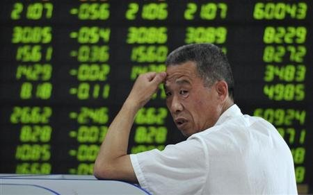 An investor looks back in front of an electronic board showing stock information filled with green-coloured figures, which indicate falling prices, at a brokerage house in Fuyang