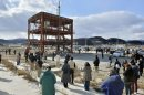 People observe a moment of silence near a tsunami-devastated disaster prevention office building in Miyagi prefecture