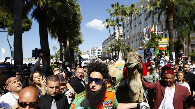 Actor Sacha Baron Cohen, centre, walks with a camel during a photo call for The Dictator at the 65th international film festival, in Cannes, southern France, Wednesday, May 16, 2012. (AP Photo/Francois Mori)