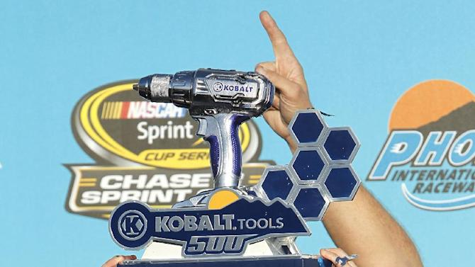 Kasey Kahne holds up his trophy after winning the NASCAR Sprint Cup Series auto race at Phoenix International Raceway, Sunday, Nov. 13, 2011, in Avondale, Ariz. (AP Photo/Ross D. Franklin)