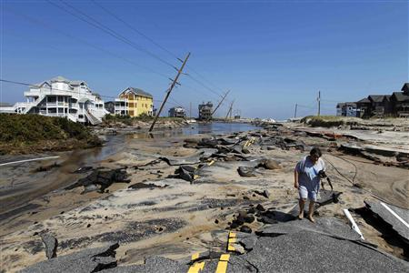 Residents walk along Highway 12, the main road that connects Cape Hatteras National Seashore to the main land was destroyed by Hurricane Irene in Rodanthe