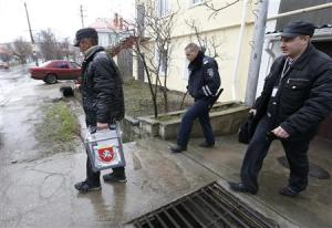An election official carries a mobile ballot box at…