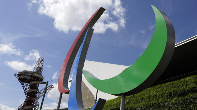 The Agitos, the official symbol design of the 2012 Paralympic Games are seen with the Orbit viewing platform artwork structure in background, as preparations are made at the Olympic Park ahead of the 2012 Paralympics, Tuesday, Aug. 28, 2012, in London.  The Paralympics will start with the opening ceremony on Aug. 29. (AP Photo/Kirsty Wigglesworth)
