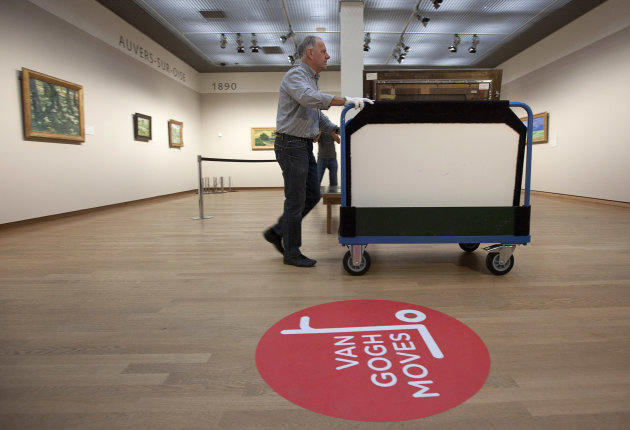 A curator removes Vincent van Gogh paintings on a carrier trolley at the Van Gogh Museum in Amsterdam, Netherlands, Sunday, Sept. 23, 2012. While the museum closes for seven months for renovations, 75 works by the Dutch painter will be displayed instead across town at The Hermitage, an Amsterdam satellite of the Russian state museum. The tricky process of transporting the artworks under police escort began immediately after the last visitors left the museum Sunday evening and carried on through the night into Monday morning. The Van Gogh Museum reopens April 25, 2013. (AP Photo/Cris Toala Olivares)