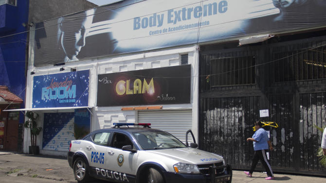 "A police car sits parked at the entrance to a gym where four people were shot dead in the Tepito neighborhood of Mexico City, Friday, June 7, 2013. Two masked gunmen stormed into the Body Extreme gym yelling ""everyone hit the floor"" and opened fire, in the Mexico City neighborhood that is home to the area's biggest black market, authorities said. Mexico City Mayor Miguel Angel Mancera said preliminary investigations indicated the killings were part of a ""personal grudge,"" and denied that the kind of large-scale drug cartel executions that have bloodied other parts of Mexico have arrived in Mexico City. (AP Photo/Gabriela Sanchez)"