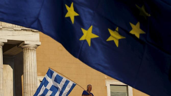 File photo of a protester waving a Greek flag at the entrance of the parliament building during a rally in Athens