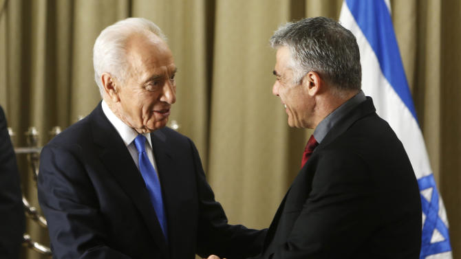 Israel's President Shimon Peres, right, shakes hands with Yair Lapid, leader of the Yesh Atid (There is a Future) party, during their meeting in Jerusalem, Wednesday, Jan. 30, 2013. Israel's two major political parties endorsed Benjamin Netanyahu for prime minister Wednesday, guaranteeing him a third term and kicking off the country's post-election process of forging a new government. The factions recommended Netanyahu to President Shimon Peres, who began consulting representatives from the major parties at his residence before deciding whom to choose as prime minister-designate to form a new coalition. (AP Phoro/Ronen Zvulun, Pool)