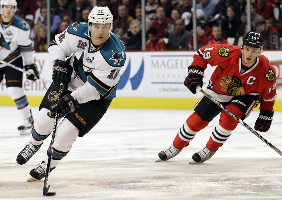 San Jose Sharks' Patrick Marleau (12) controls the puck as he looks to make a pass past Chicago Blackhawks' Jonathan Toews (19) during the first period of an NHL hockey game in Chicago, Friday, Feb. 22, 2013. (AP Photo/Nam Y. Huh)