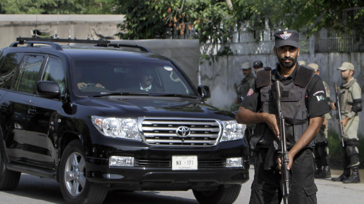 A Pakistani police commando stands guard as a vehicle carrying former President and army chief Pervez Musharraf arrives to appear at an anti terrorism court in Rawalpindi, Pakistan, Tuesday, Aug. 20, 2013. A Pakistani court Tuesday indicted Musharraf on murder charges in connection with the 2007 assassination of iconic Pakistani Prime Minister Benazir Bhutto, deepening the fall of a once-powerful figure who returned to the country this year in an effort to take part in elections. (AP Photo/Anjum Naveed)