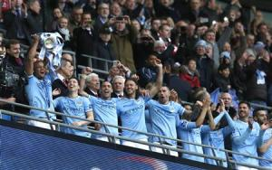 Manchester City captain Kompany holds aloft the trophy after defeating Sunderland to win the English League Cup final soccer match at Wembley Stadium in London