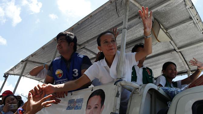 Presidential candidate Grace Poe waves as supporters reach out to her during election campaigning in General Mariano Alvares, Cavite