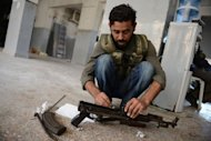 A rebel fighter cleans his gun during fighting against pro-Syrian government forces in the Bustan al-Bashar district of the northern Syrian city of Aleppo