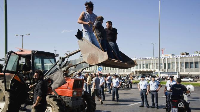 Protesting farmers use tractors to block the entrance of the Iraklio International Airport, Crete, Greece on Thursday, Oct. 4, 2012. The Cretan farmers, protesting pension cuts expected under new Greek austerity measures, attempted to block access to the airport, using tractors and other farm vehicles. Police used tear gas against the protesters who had gathered from across the island. (AP  Photo/Bastian Parschau)