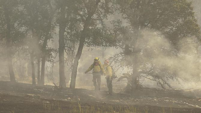 Firefighters walk below smoke off of Morgan Valley Road near Lower Lake, Calif., Friday, July 31, 2015. The golden hills of California were being blackened Friday by a series of wildfires egged on by bone-dry vegetation, triple-digit temperatures and gusting winds. (AP Photo/Jeff Chiu)