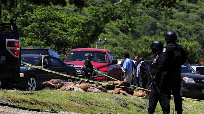 EDS NOTE GRAPHIC CONTENT - Mexican federal police secure the area where 17 dismembered bodies were found by a highway in the town of Tizapan el Alto near the border between Jalisco and Michoacan states, Mexico, Sept. 16, 2012. The Jalisco state prosecutor, Tomas Coronado Olmos, didn't reveal the identities of the slain but said the bodies were naked, mutilated and stacked with chains around their necks. (AP Photo/Bruno Gonzalez)