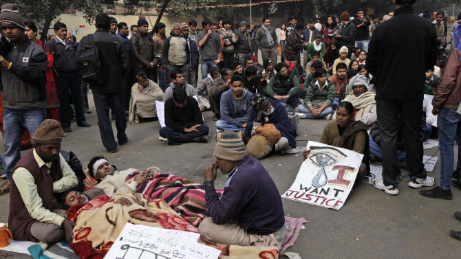 "Indian men lie on a street while on a hunger strike during a protest in New Delhi, India, Monday, Dec. 31, 2012. A young woman who died after being gang-raped and beaten on a bus in India's capital was cremated privately as millions of grieving, angry residents demanded greater protection for women from sexual violence. A placard in front reads as, ""Against women harassment, 8th day of Hunger Strike.""  (AP Photo/Manish Swarup)"