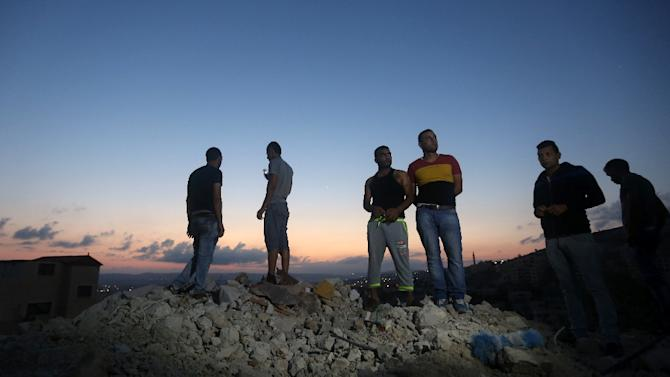 Palestinians stand on the rubble of a house which was demolished by Israeli security forces during an overnight raid in the West Bank city of Jenin, on September 1, 2015