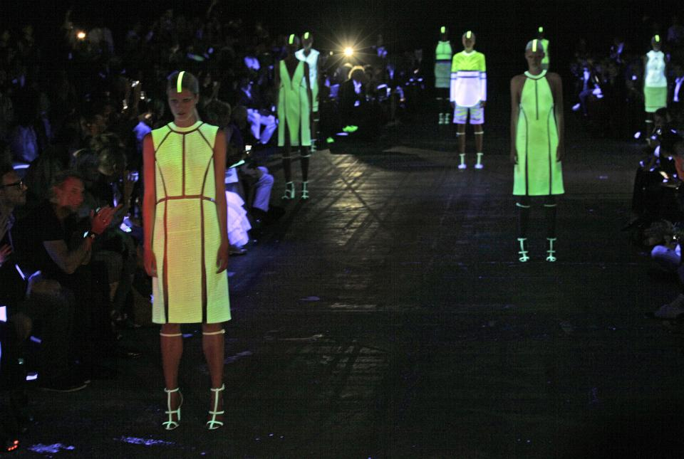 Models, illuminated by black light, pose in the finale of the Alexander Wang Spring 2013 collection, during Fashion Week in New York,  Saturday, Sept. 8, 2012. (AP Photo/Richard Drew)