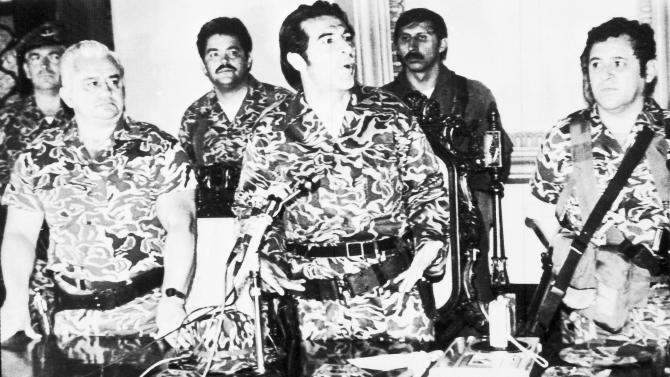 FILE - In this March 23, 1982 photo, General Efrain Rios Montt, center, speaks at a press conference in Guatemala City, where he announced the formation of a junta in the aftermath of the overthrow of General Fernando Romeo Lucas Garcia's right wing government. At left is General Horacio Maldonado Shad and right is Colonel Luis Frandisco Gordillo. Rios Montt rose to power in this March 23, 1982 coup d'etat, holding absolute power for just over a year before he himself was overthrown.  Rios Montt has ruled as Guatemala's dictator, served as president of Congress, preached as an evangelical pastor and now, at 87, has become the first Latin American strongman to stand trial on genocide charges in his own country. (AP Photo, File)